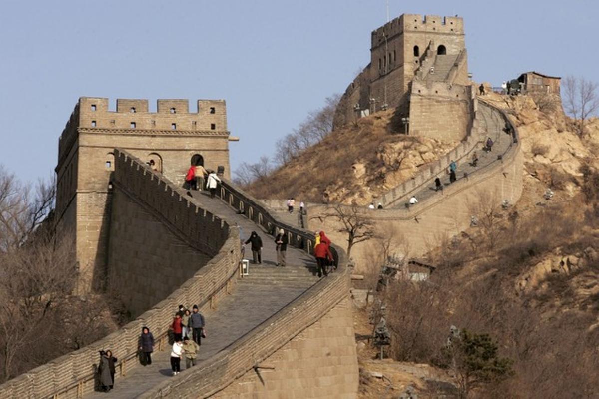 Un grupo de turistas caminan por un tramo de la gran muralla.