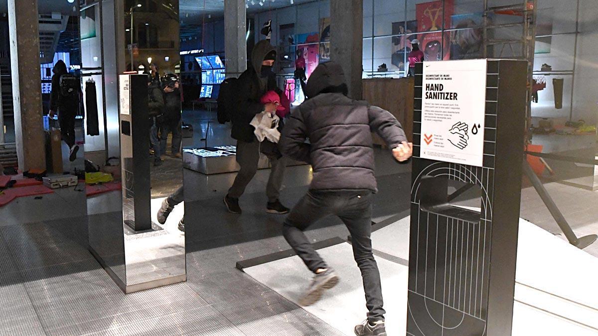Participantes en las protestas entran en una tienda en Barcelona