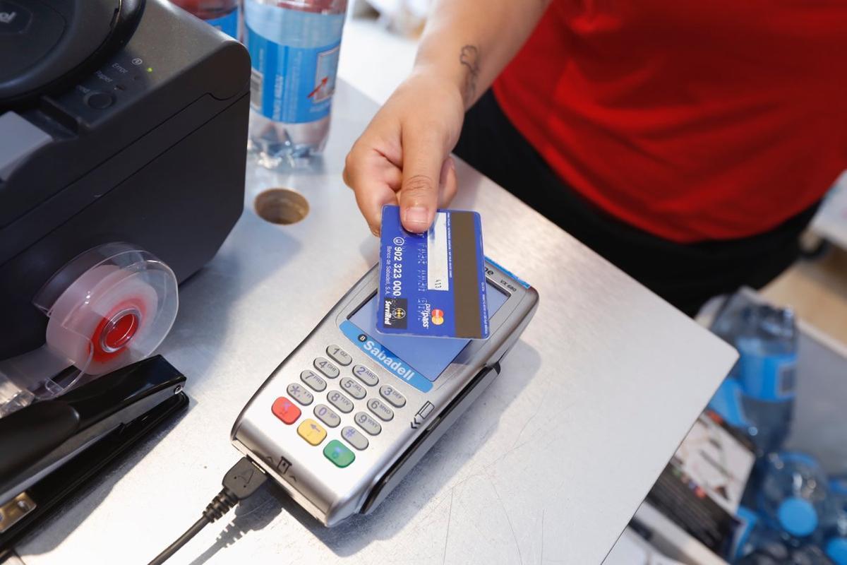 Un usuario paga en el TPV de un comercio con una tarjeta.