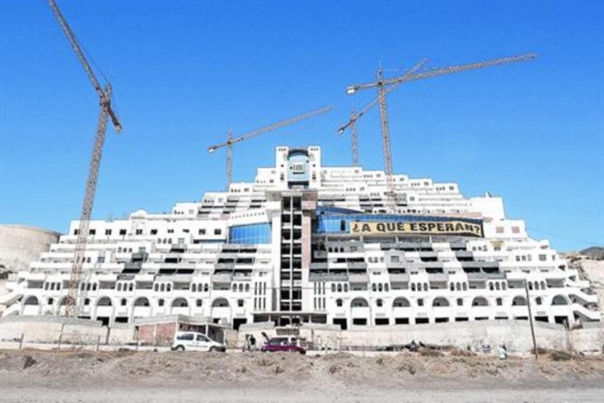 El hotel inacabado del Algarrobico, en la playa almeriense de Carboneras, con una pancarta que llama a su demolición, en el 2012.