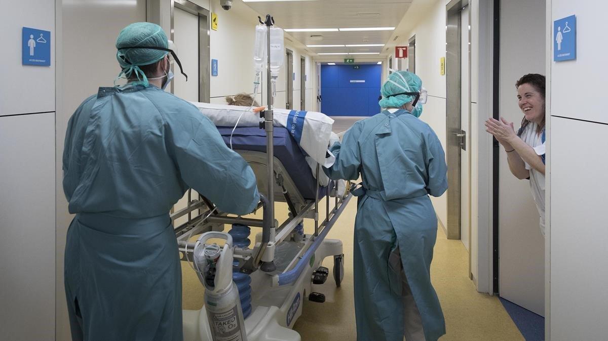 Sanitarios de la Vall d'Hebron aplauden a una mujer dada de alta de la uci.