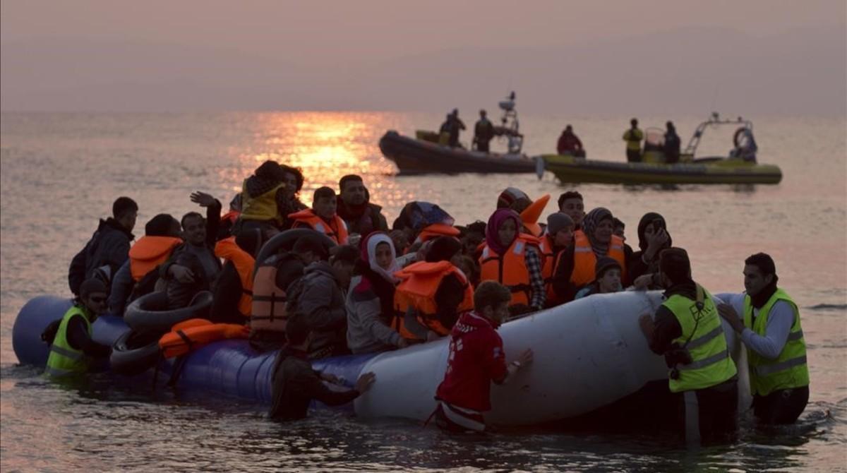 Varios voluntarios ayudan a refugiados a su llegada a la isla de Lesbos.