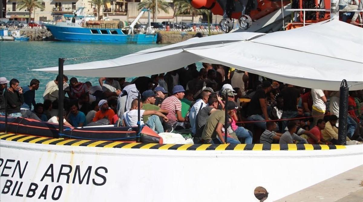 Unos inmigrantes esperan desembarcar de uno de los barcos de Open Arms.