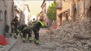 Bomberos buscan entre los escombros en Norcia.