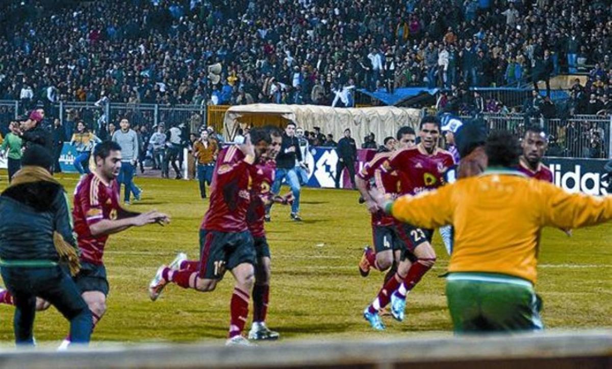 Los jugadores cairotas corren hacia los vestuarios al final del partido, perseguidos por los hinchas locales.