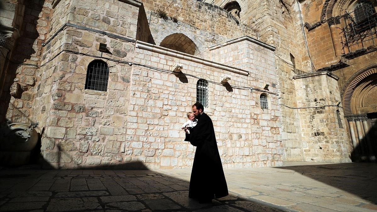Un sacerdote cristiano camina con un niño en brazos por la plaza de la iglesia del Santo Sepulcro, este domingo en Jerusalén.