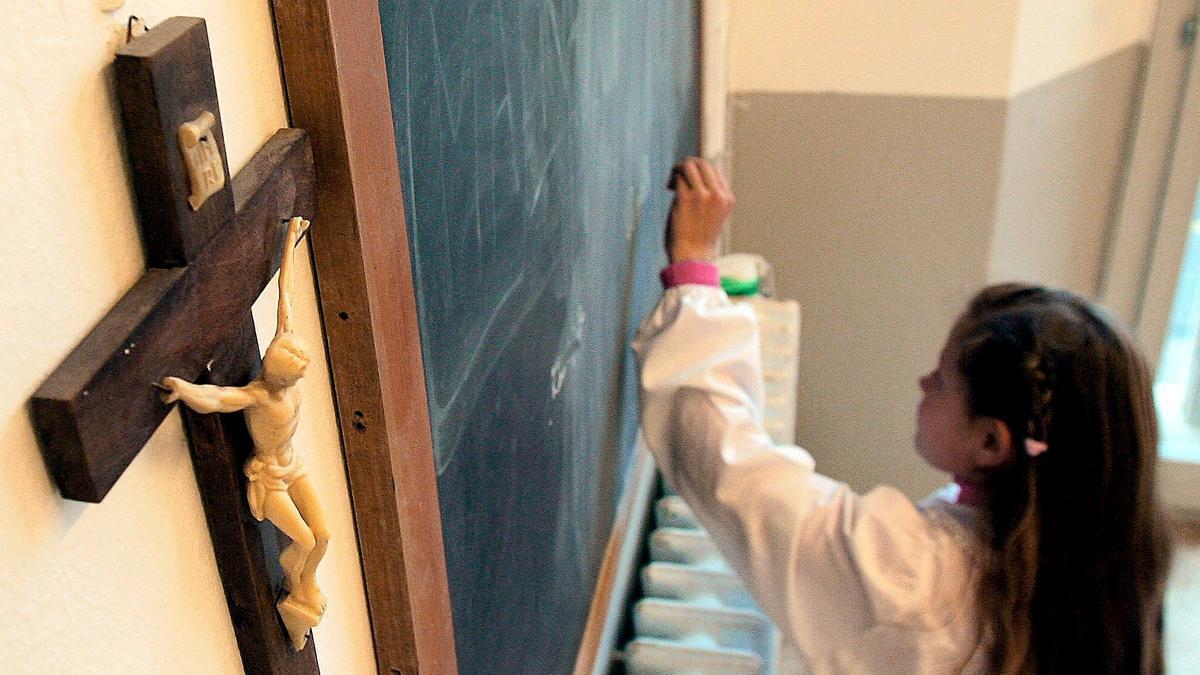 Una estudiante escribe en la pizarra de una clase que tiene un crucifijo colgado en la pared.