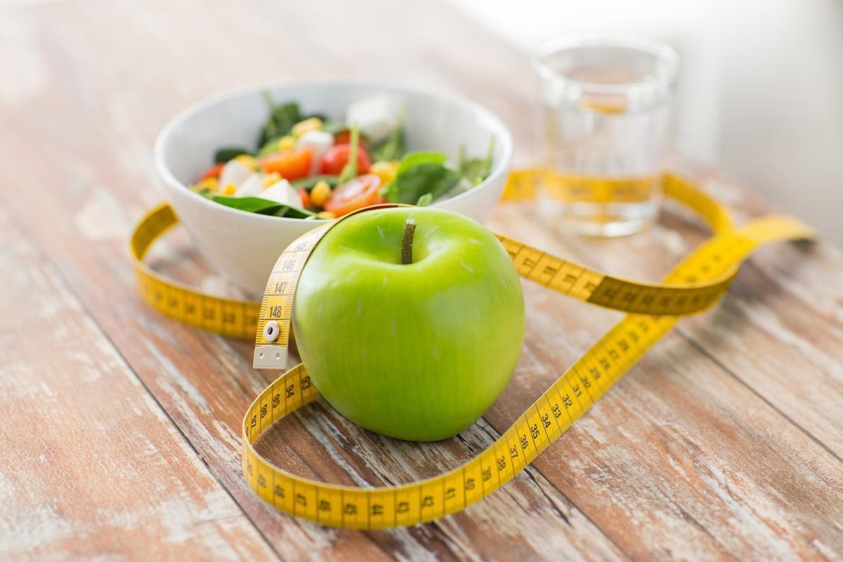 Manzana, cinta métrica y desayuno en una mesa.