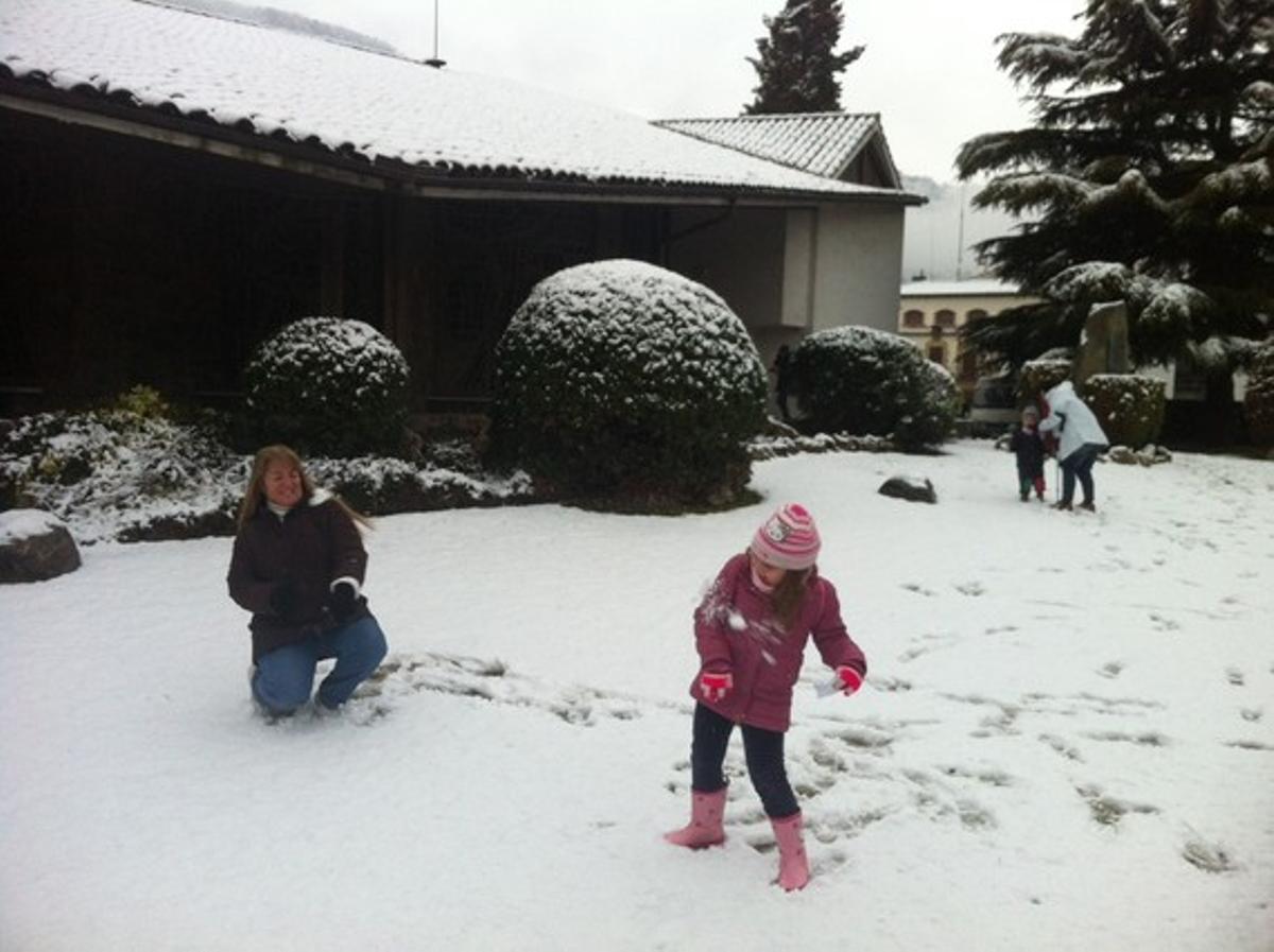 Una niña y su madre juegan con la nieve en su casa de Aiguafreda.