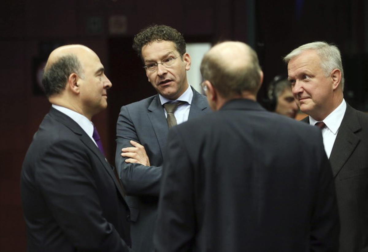 El ministro francés de Finanzas, Pierre Moscovici (izquierda), conversa con el presidente del Eurogrupo, Jeroen Dijsselbloem, y el comisario Olli Rehn, antes del inicio de la reunión de ministros de Finanzas de la UE, este viernes.