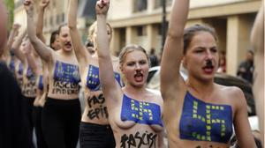 Les activistes desfilen pels carrers de París amb esvàstiques i la bandera de la UE pintades al pit.