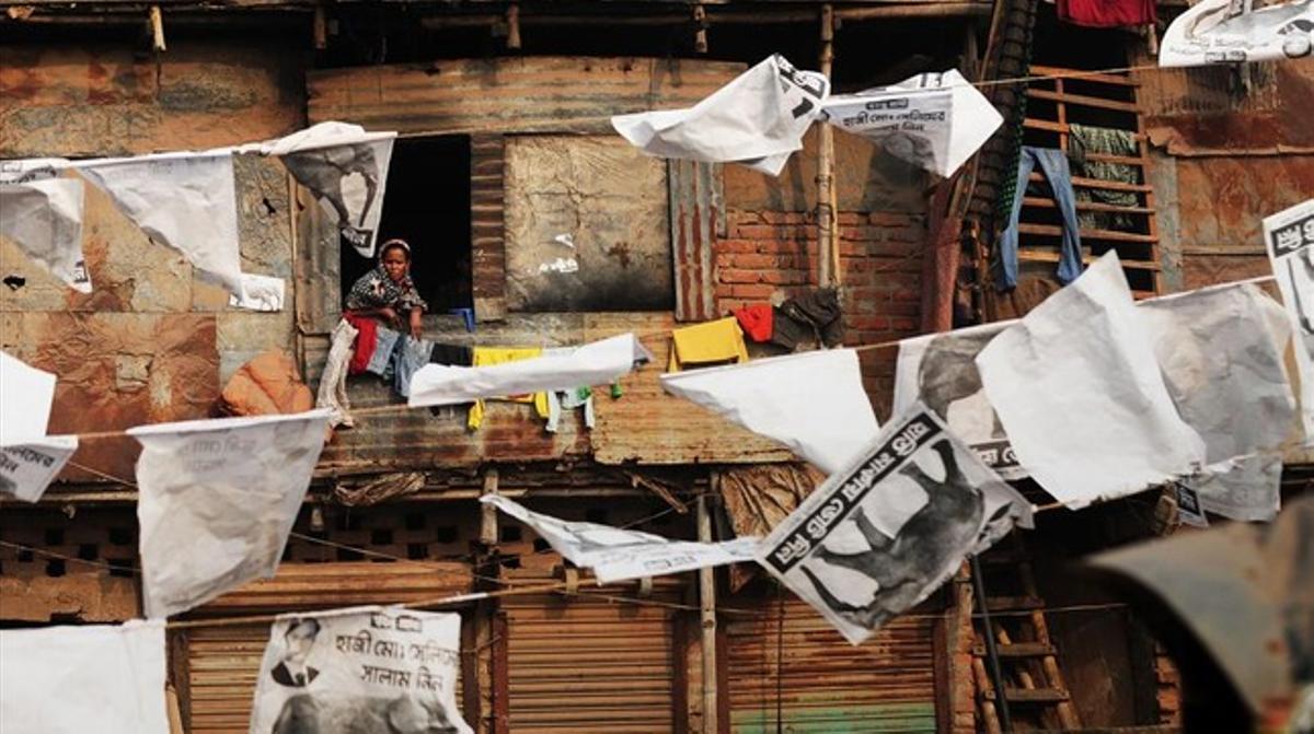 Vecinos del barrio de Shanty, Bangladesh, rodeados de publicidad electoral.