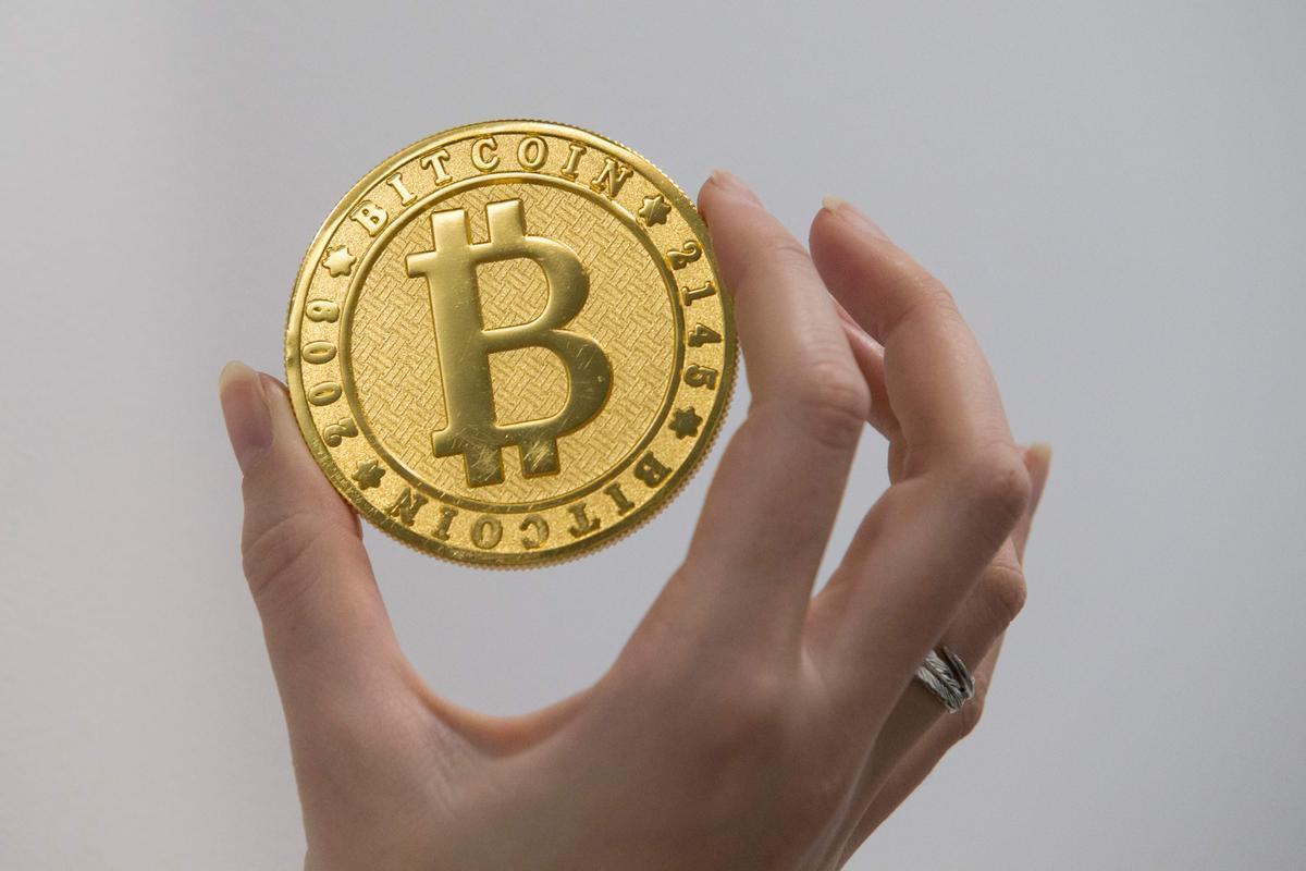 Una persona sostiene una representación visual de la criptomoneda digital Bitcóin, en La Maison du Bitcoin en París.