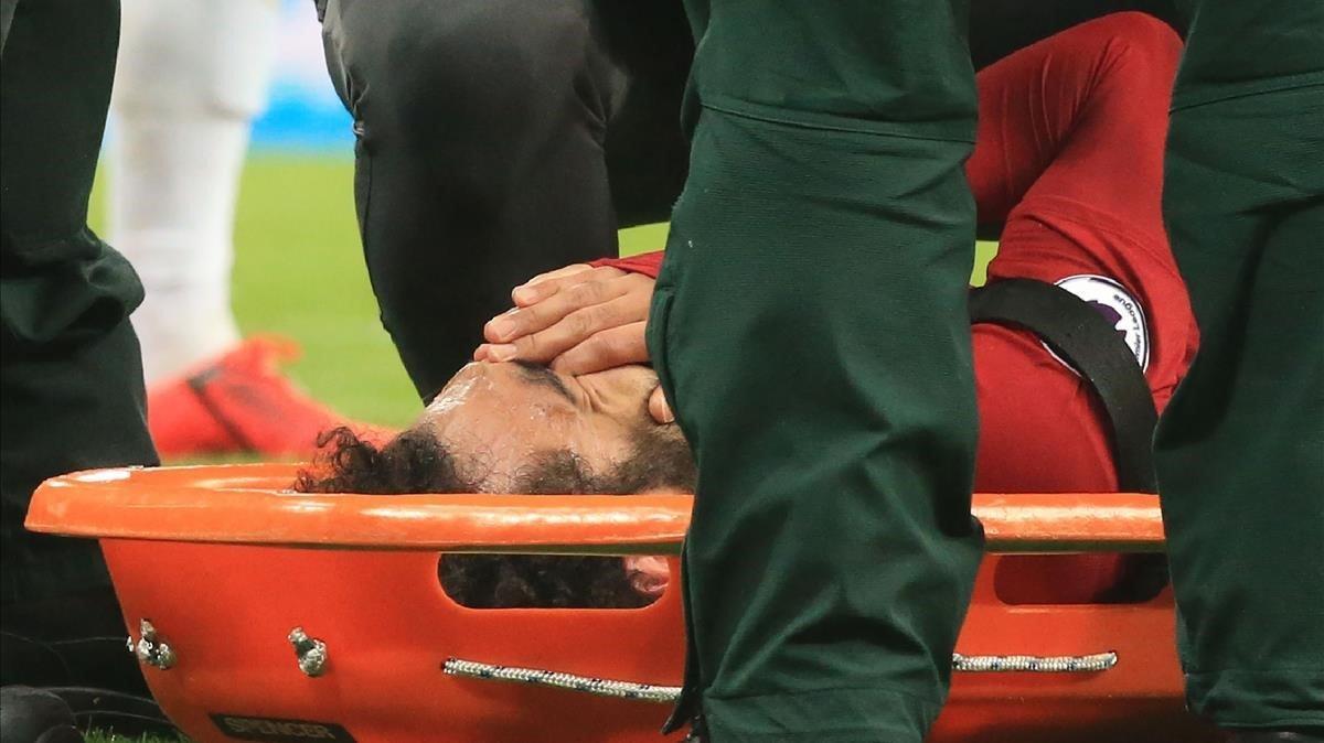Salah se lleva las manos a la cara mientras es atendido en la camilla sobre el césped.
