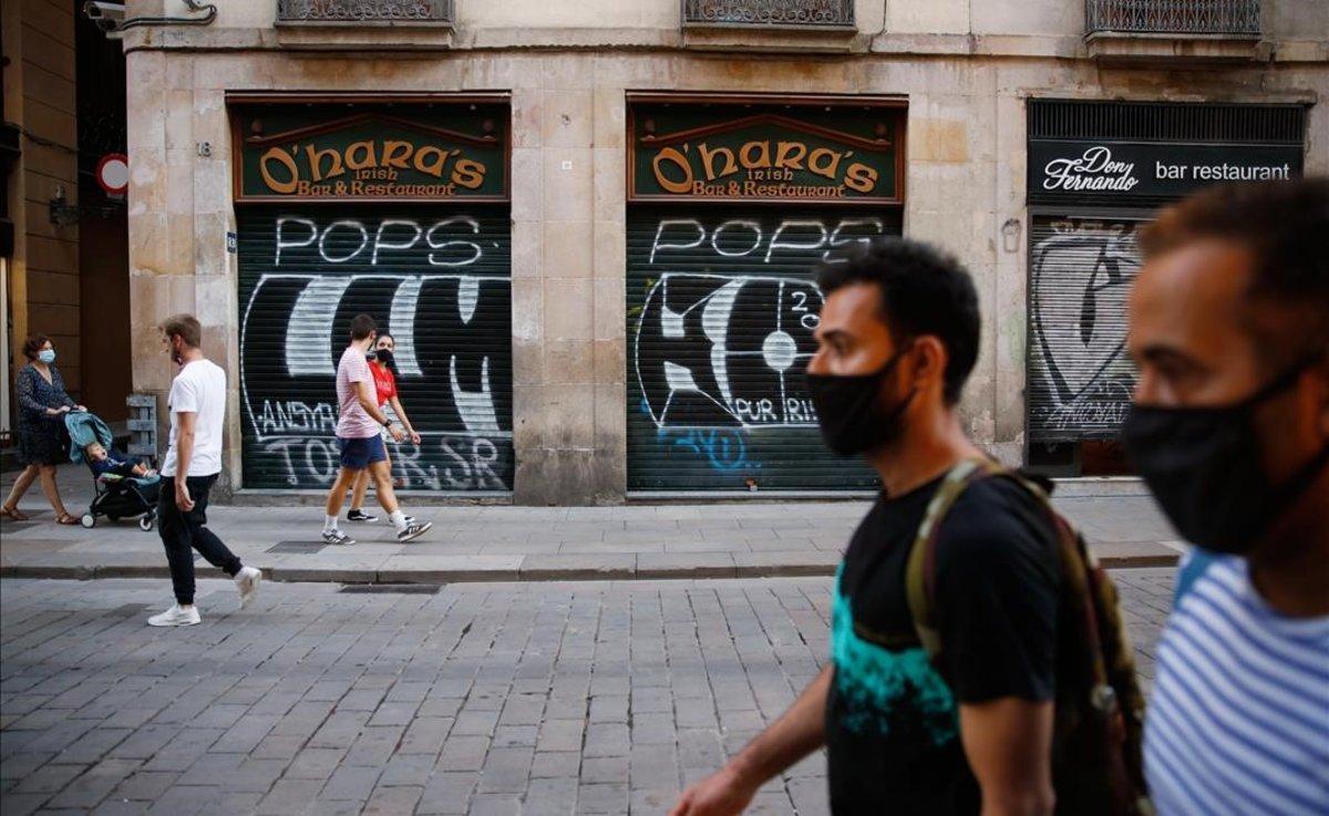 Dos hombres con mascarilla, en una calle céntrica de Barcelona con los comercios cerrados.