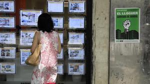 Cartel de la manifestación junto a una inmobiliaria, en la calle de Sants.
