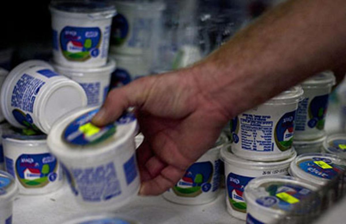 Un consumidor coge un recipiente de requesón en un supermercado de Jerusalén.