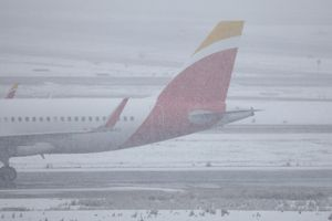 Un avión espera en el aeropuerto de Barajas bajo la nieve.