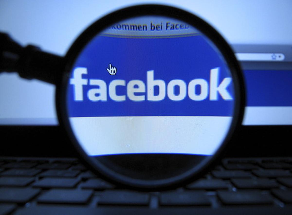 El logotipo de Facebook, visto a través de una lupa.