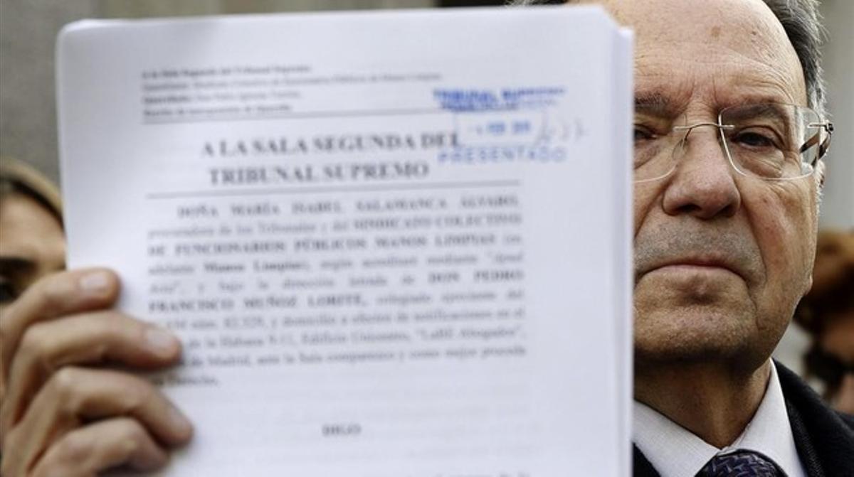 El secretario general de Manos Limpias, Miguel Bernard, con una copia de la querella que ha presentado este miércoles ante el Supremo contra Pablo Iglesias.