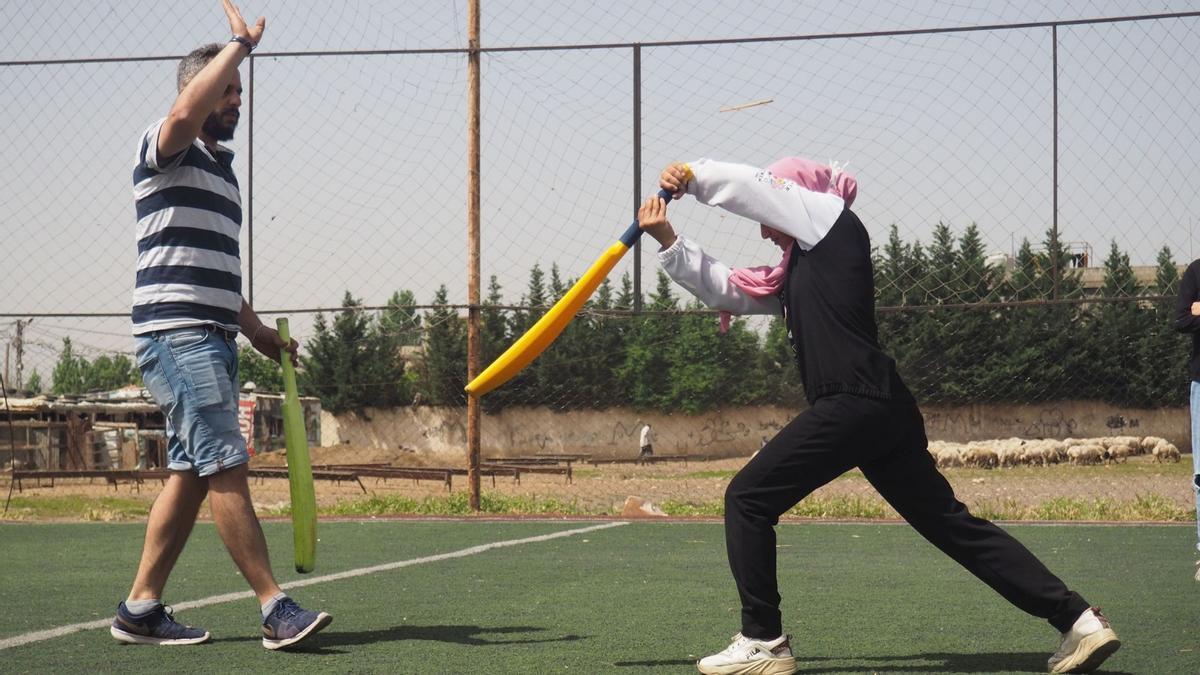 Aya, de 13 años, practica su push mientras la corrige Mohammed Kheir, entrenador y jefe del programa de críquet de Alsam.