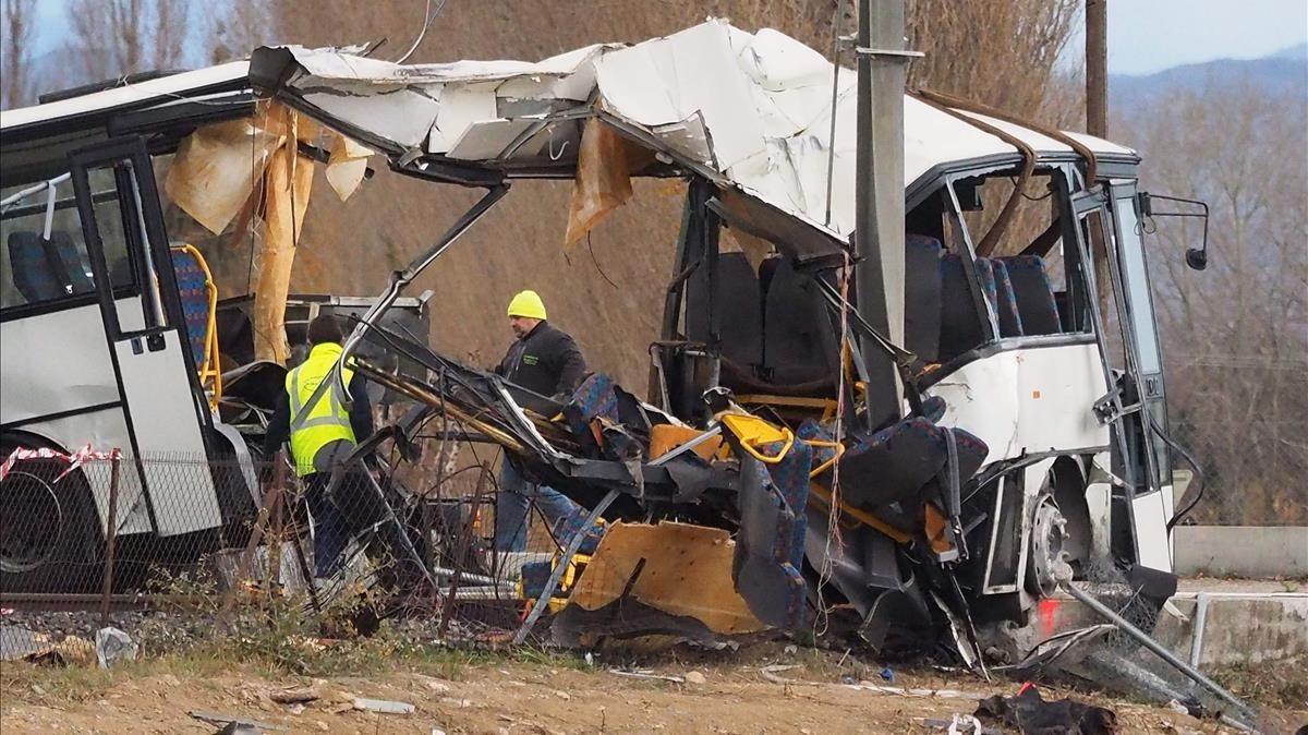 Operarios junto al autobús escolar destrozado por el impacto de la colisión con un tren en Millas, cerca de Perpinyà, el 15 de diciembre.