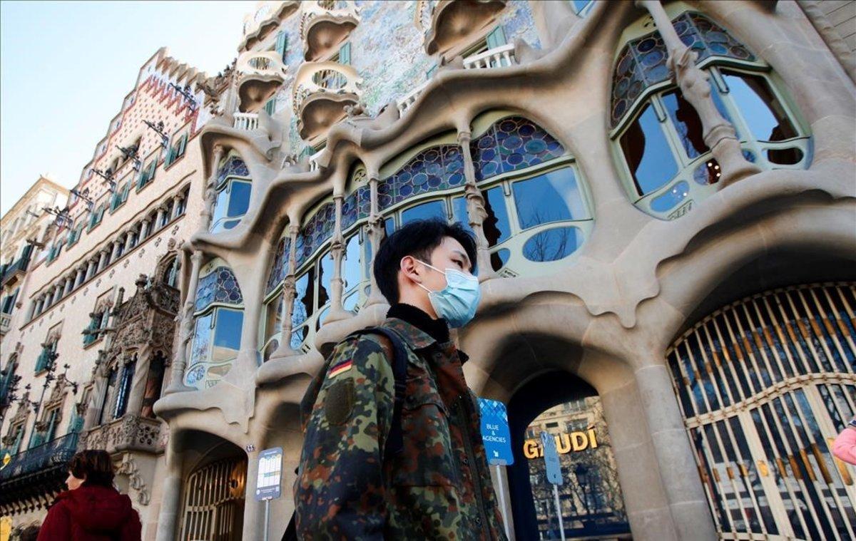Un turista con mascarilla para evitar el contagio por coronavirus, frente a la Casa Batlló, en Barcelona.