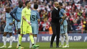 Guardiola consuela a sus jugadores al final del partido, este domingo en Wembley.