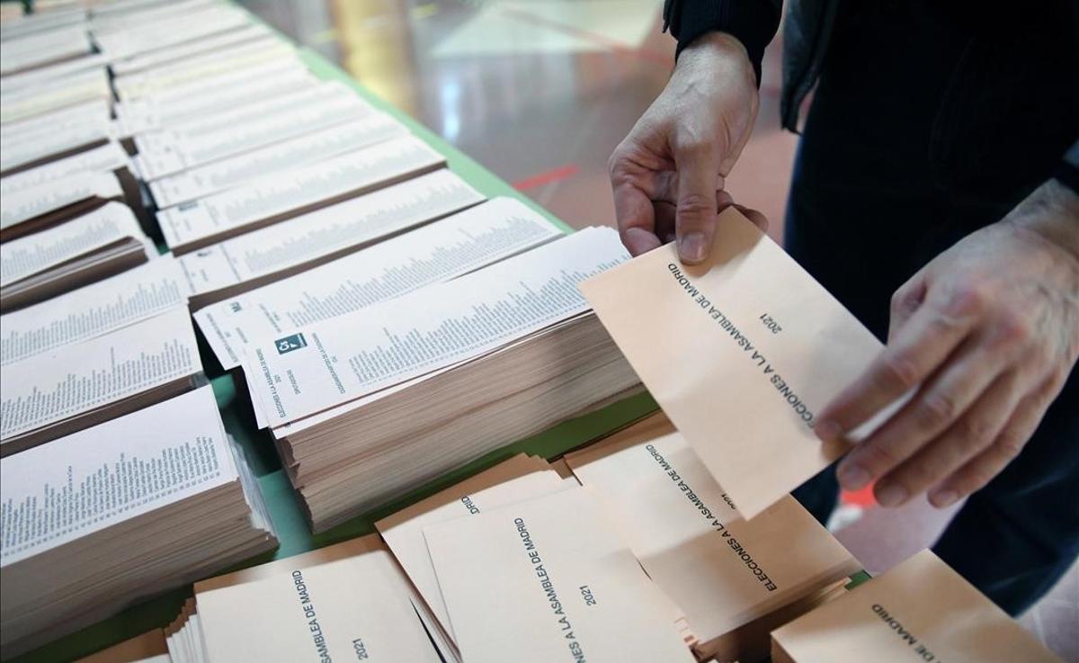 Un miembro de la mesa electoral coloca una mesa con papeletas momentos antes de la apertura del colegio Roma de Madrid.
