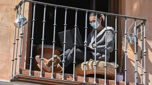 Imagen de archivo de una mujer trabajando en el balcón de su casa en plena cuarentena.