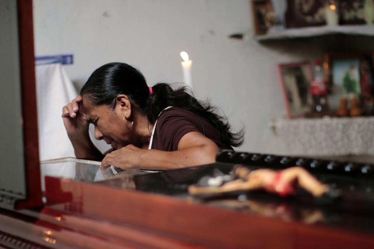 Una mujer llora sobre el féretro de Miguel Ángel Jiménez, este domingo en Xaltianguis.