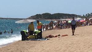 Equipo del SEM al lado del hombre que ha fallecidoahogado este lunes en la playa Gran de Platja d'Aro.