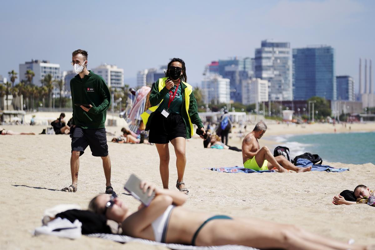 Dos informadores en el control de aforo en la Playa de Bogatell este jueves.
