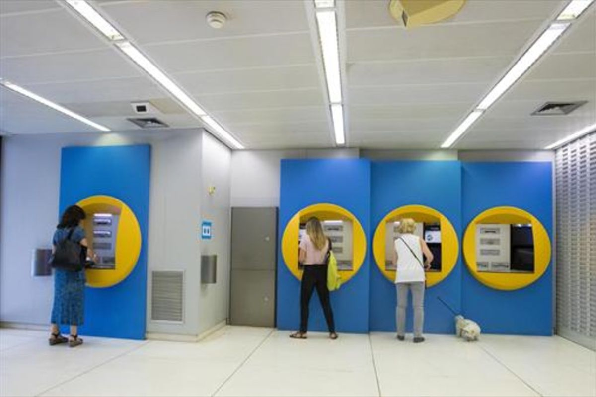 Clientes en cajeros de CaixaBank en la sede Barcelona.