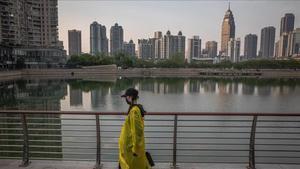Una mujer camina junto a un lago en Wuhan, origen de la epidemia de coronavirus en China.