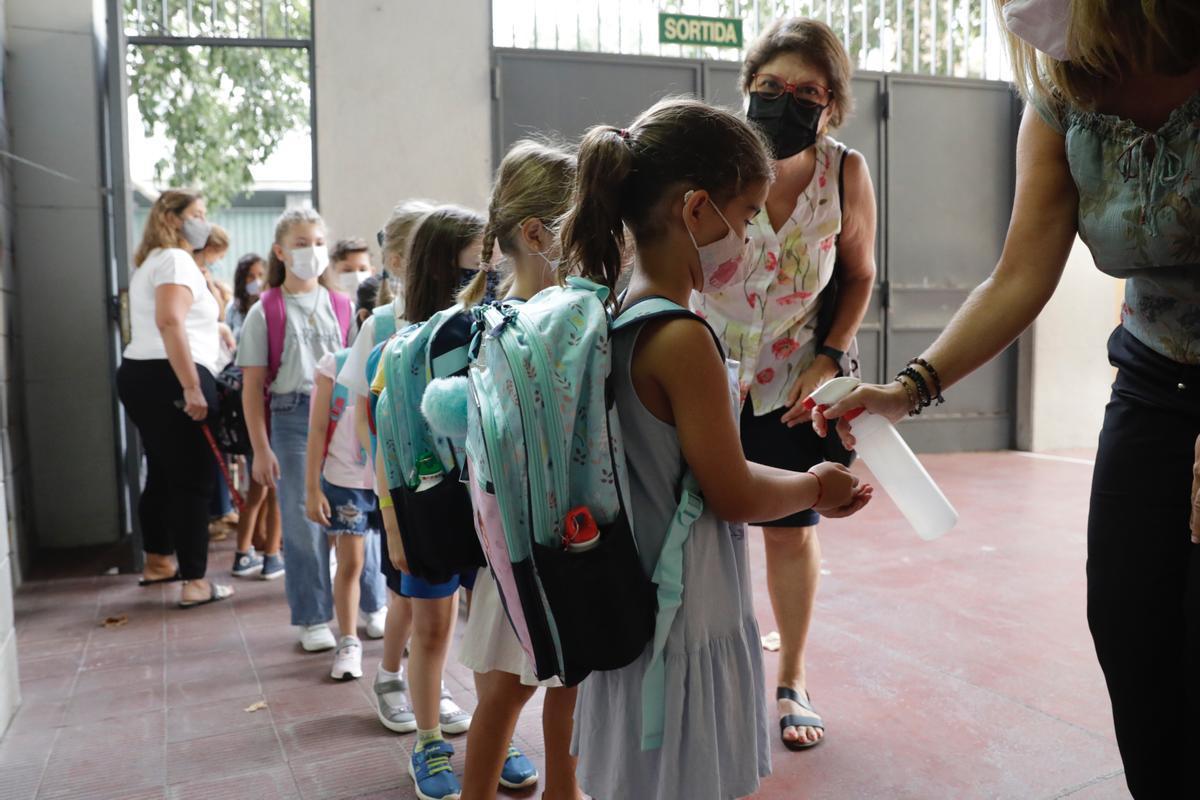 Alumnos del Institut Escola Londres, en Barcelona, se ponen gel hidroalcohólico antes de entrar en clase.