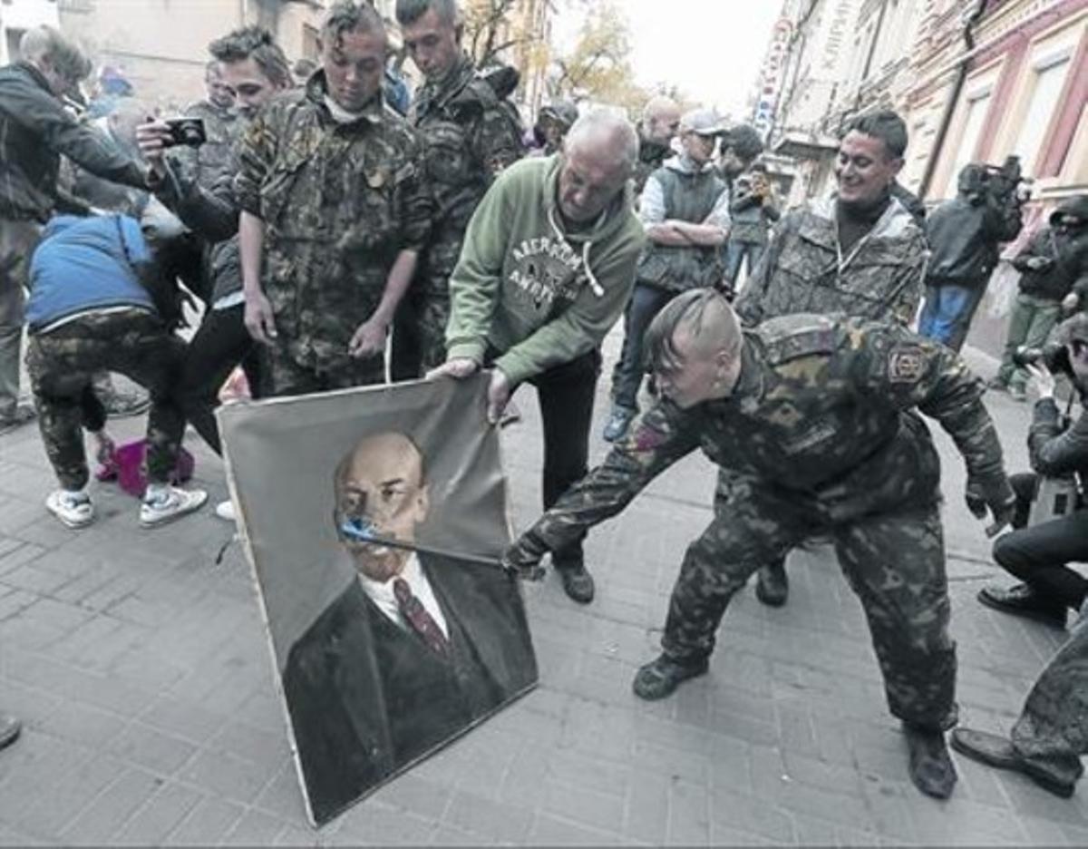 Un miliciano de Maidán  daña un retrato de Lenin, el pasado 9 de abril.