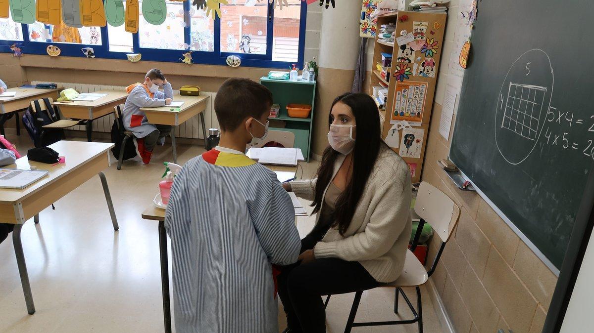 Una profesora haciendo uso de la mascarilla transparente en clase.