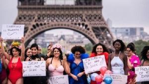 Varias modelos exhiben carteles reivindicativos tras desfilar en la pasarela 'All sizes catwalk' en París.