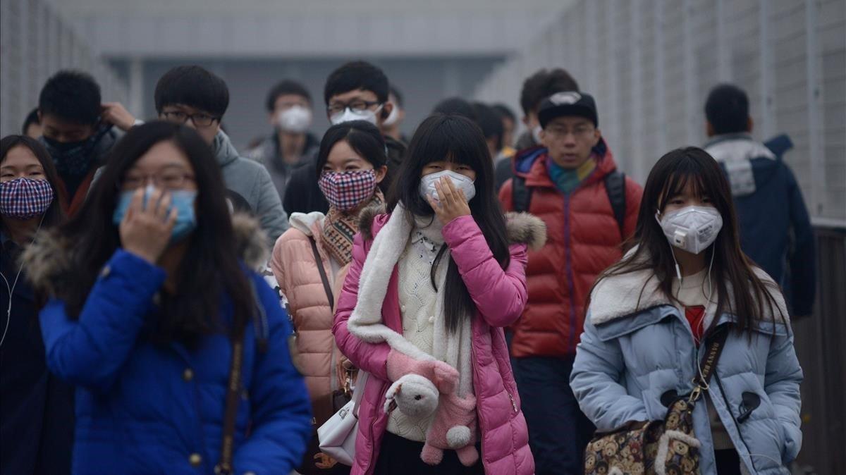 En Pekín, los peatones utilizan mascarillas durante un episodio de alerta de contaminación