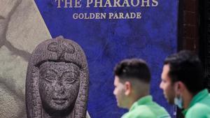 Dos hombres contemplan el cartel del desfile de los faraones, en El Cairo.