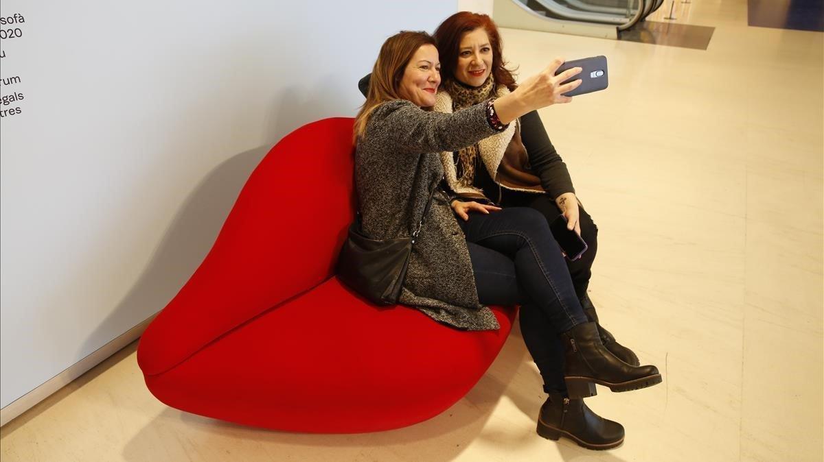 Dos visitantes de la exposición 'Objetos de deseo' de CaixaFòrum se fotografían en el acceso a la misma.