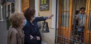Carmen, acompañada de su cuñada, saluda a su marido, Antonio, que vive en una residencia de València.