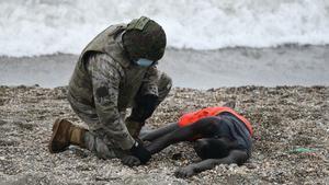 Un militar del ejército español ayuda a una persona tumbada en la orilla en una jornada marcada por las devoluciones en caliente que están efectuando a los migrantes que han entrado en Ceuta.