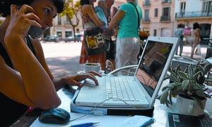 Una dona consulta internet en un portàtil mentre conversa pel mòbil, en una terrassa de Barcelona.