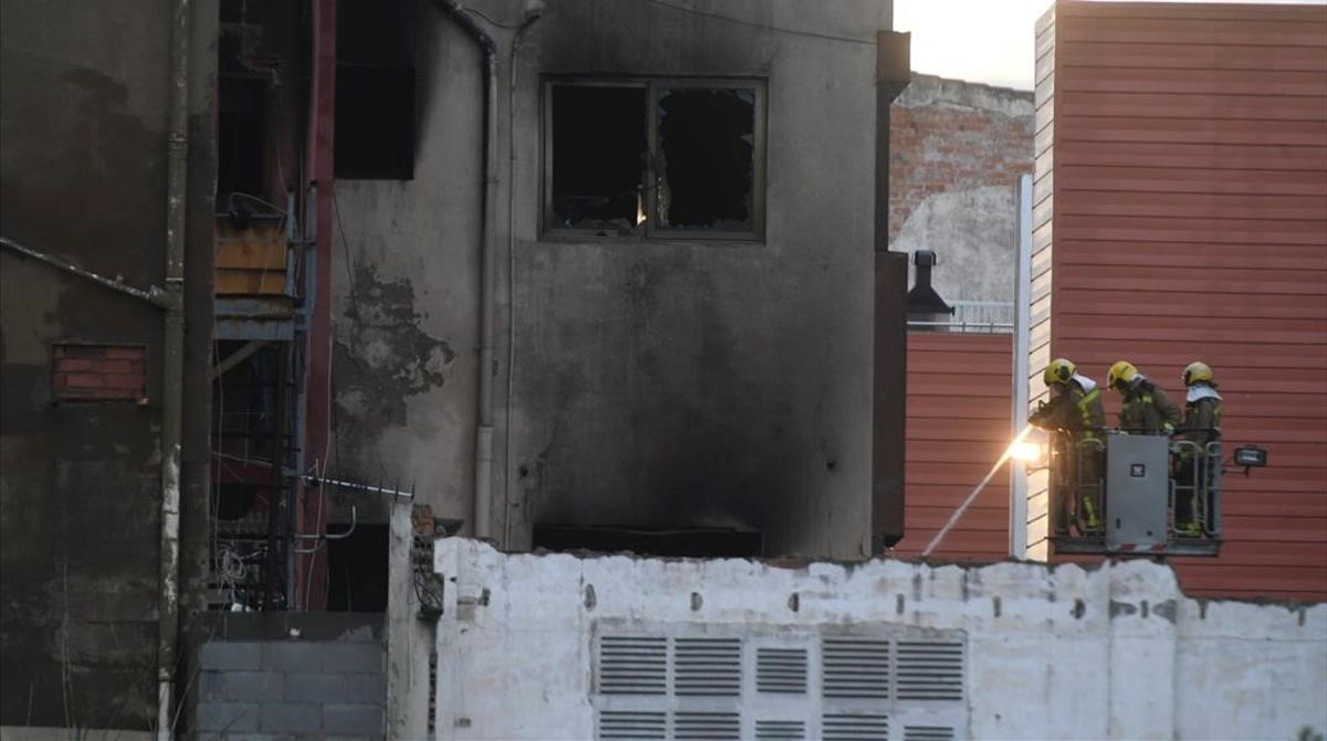 Los bomberos trabajan en la extinción del incendio de la nave ocupada en Badalona.