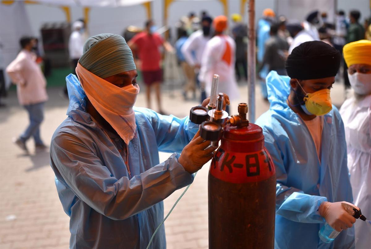 Un sanitario rellena una bombona de oxígeno en un puesto de atención médica en Nueva Delhi.