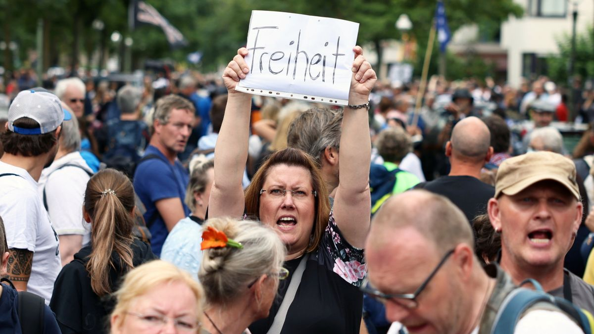 Una manifestante en Berlín protesta contra las restricciones y alza una pancarta que pone libertad.