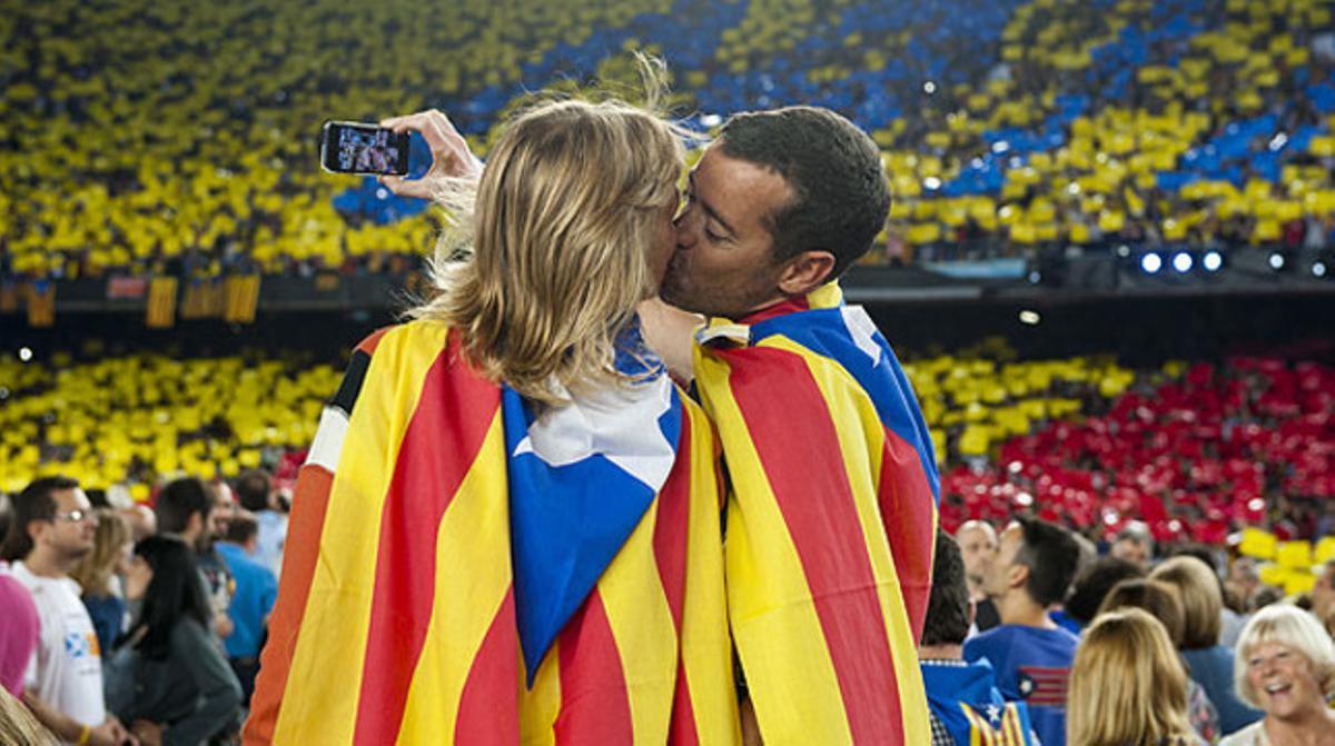 Una pareja con dos 'estelades' a modo de capa se besa en el Camp Nou.