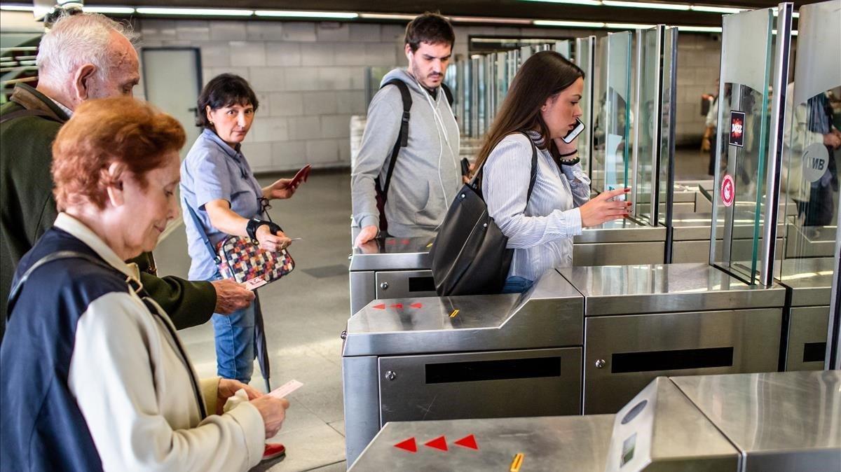 Unos usuarios del metro validan sus billetes, en octubre.
